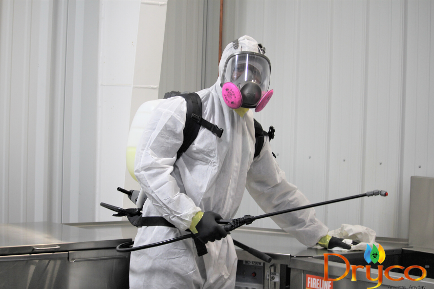 Dryco employee in protective equipment wiping down surfaces affected by Covid-19